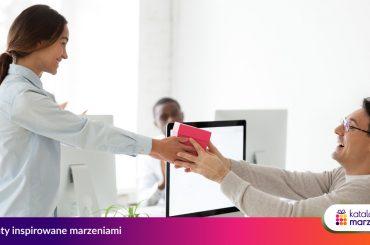 Manager wręcza pracownikowi voucher na przeżycie