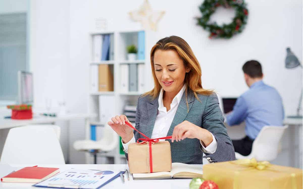 Kobieta rozpakowuje prezent świąteczny