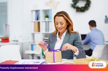 Pracownik otwiera prezent świąteczny w biurze