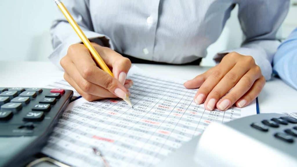 Kobieta wypełnia tabelę podatkową i rozlicza prezenty dla pracowników
