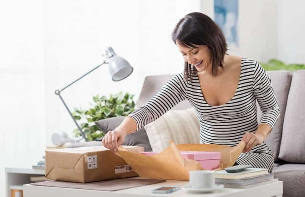 Kobieta klientka otwiera prezent, który otrzymała od przedsiębiorcy w ramach zgłoszonej reklamacji