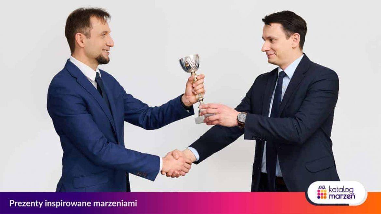 Mężczyzna wręcza zwycięzcy nagrodę w konkursie w postaci pucharu z gratulacjami