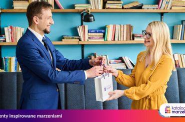 Mężczyzna wręcza voucher na prezent kobiecie, z którą współpracuje