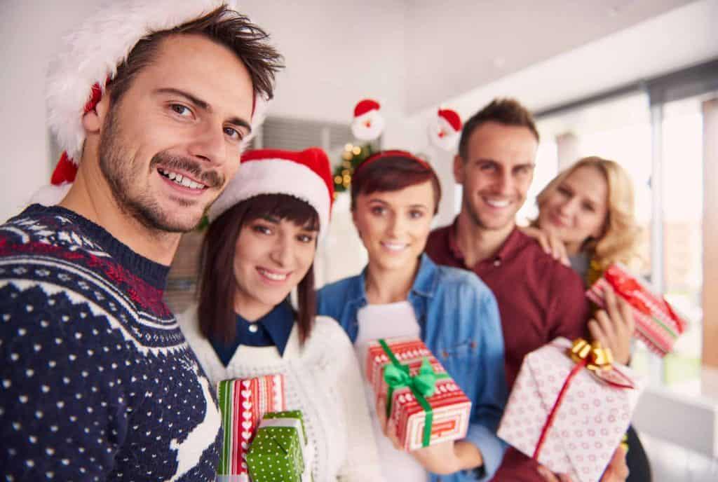 Pracownicy firmy trzymają prezenty bożonarodzeniowe dla klientów